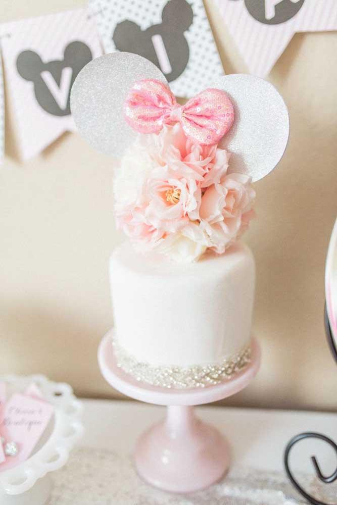 Um bolo da Minnie super delicado e romântico em tons de branco e rosa decorado com mini pérolas e flores