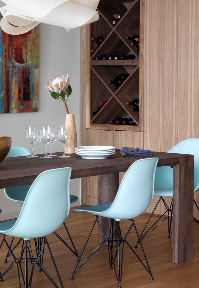 A mesa para sala de jantar de madeira rústica foi contrastada com as cadeiras modernas