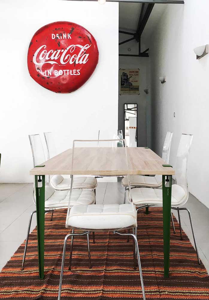 Moderna, essa mesa de jantar apostou em um tampo de madeira clara com pés de ferro na cor verde. As cadeiras de acrílico transparente fecham a proposta
