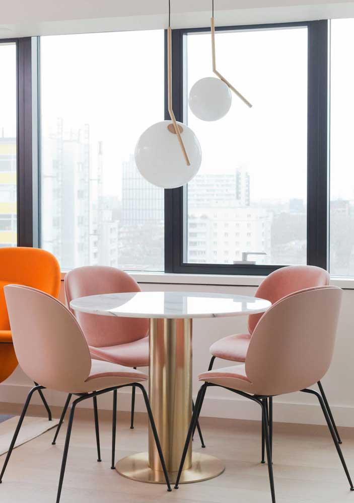 A base dourada dessa mesa de jantar redonda reforça o visual delicado e ao mesmo tempo moderno da decoração