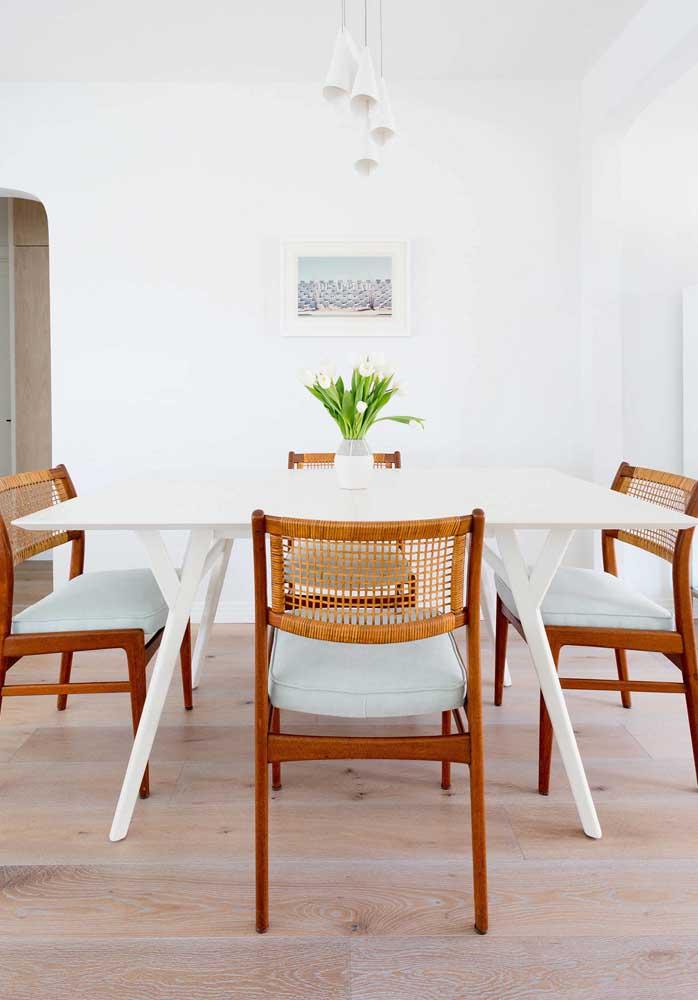 Cadeiras de fibra contrastadas pela mesa de jantar branca