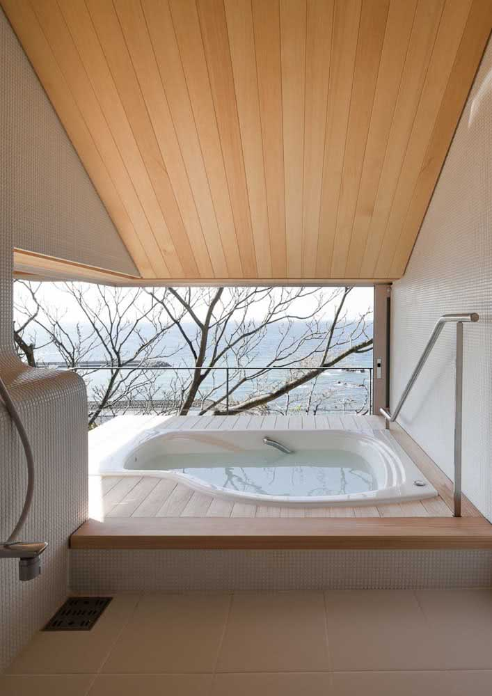 Jacuzzi com deck de madeira. Lá fora, a paisagem completa o momento do relaxamento