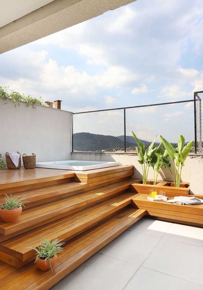 Jacuzzi com deck de madeira e algumas plantas para tornar o ambiente ainda mais aconchegante