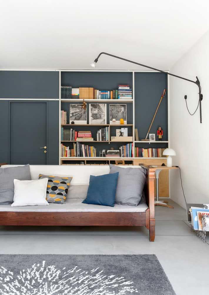 A parede de cor escura realça a presença da estante