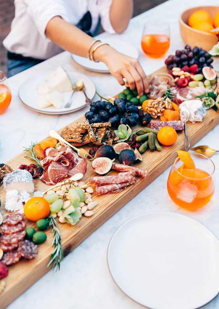 Uma tábua grande de madeira dá conta de acomodar tudo o que a noite de queijos e vinho precisa