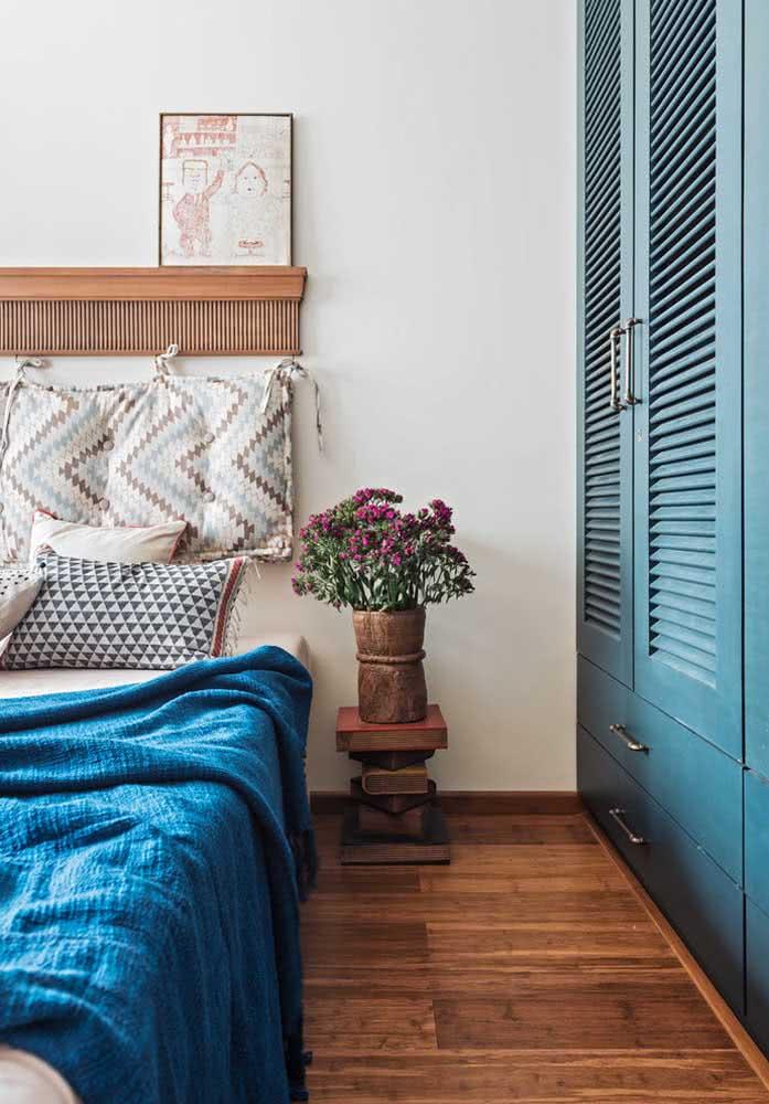 O guarda-roupa azul traz um clima rústico e acolhedor ao quarto