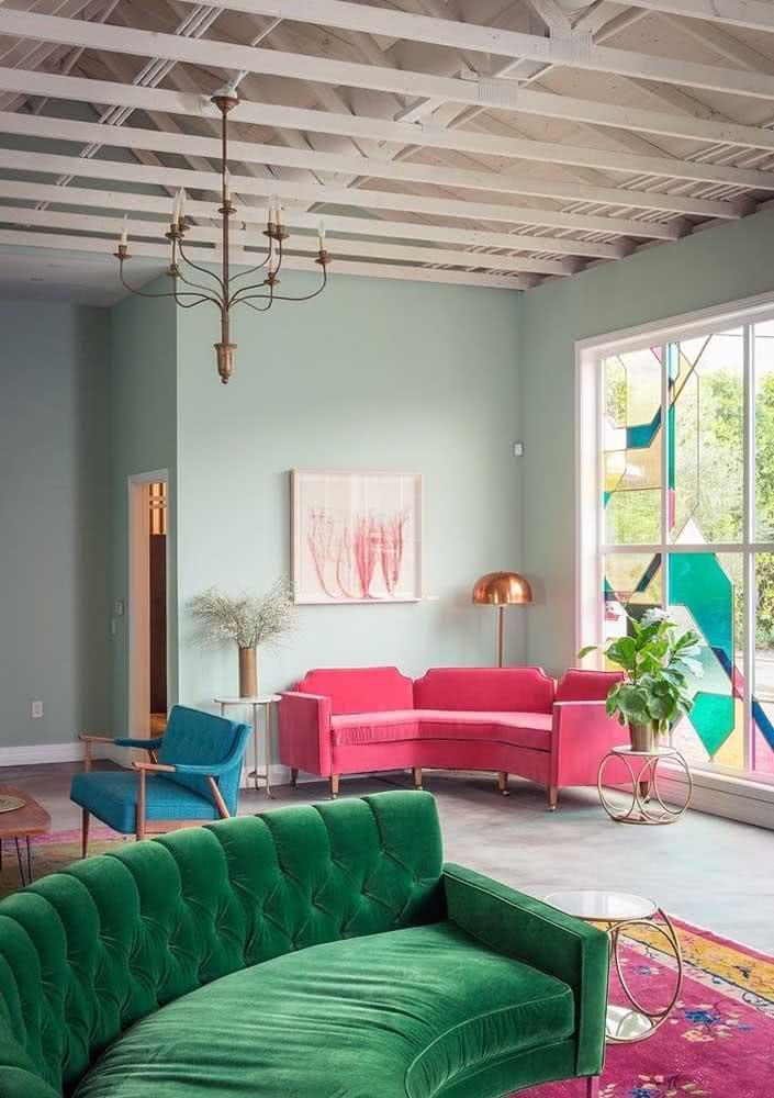 Sofá rosa de canto formando um lindo conjunto visual com o sofá verde de veludo mais a frente
