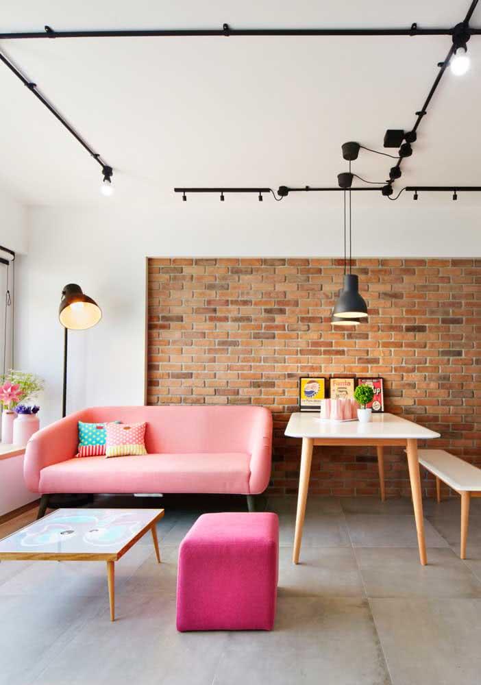 O sofá rosa fica incrível combinado com a parede de tijolinhos