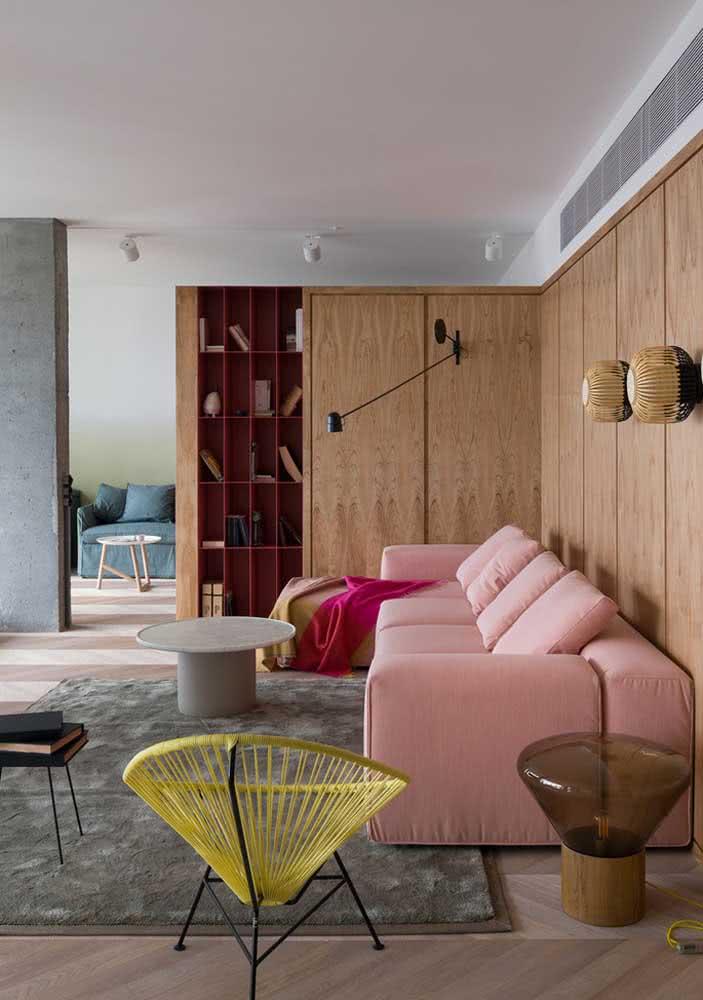 Que tal combinar um sofá rosa de design moderno com painel de madeira e cadeira Acapulco amarela?