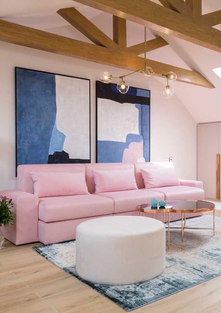 Sofá rosa claro na sala de tons de azul, branco, dourado e detalhes em madeira