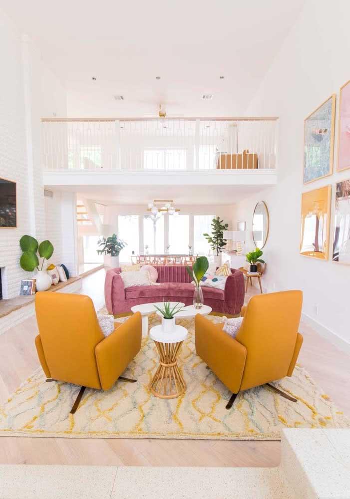 Sala de estar com sofá rosa de veludo, poltronas mostarda e um leve toque de verde trazido pelas plantas