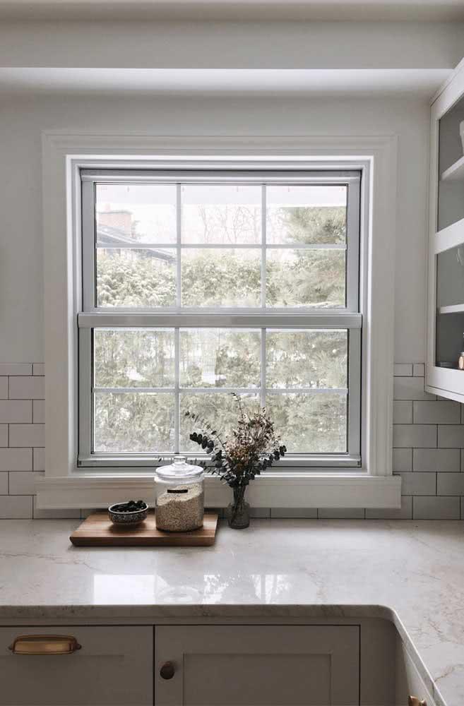 Janela guilhotina branca para combinar com a cozinha de azulejos, armários e mármore branco