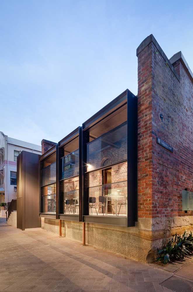 Janela guilhotina moderna em contraste com a rusticidade da parede de tijolinhos