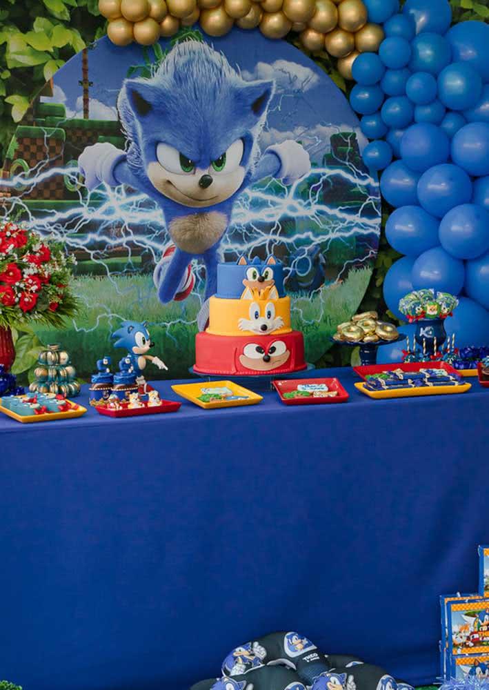 Mesa do bolo para Festa Sonic. A toalha azul forma o cenário perfeito para destacar os doces
