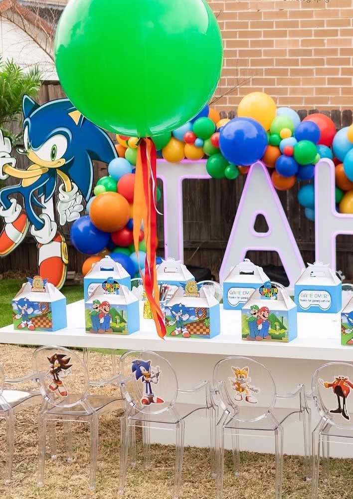 Festa Sonic ao ar livre. A mesa posta traz uma sacolinha para cada convidado e as cadeiras são marcadas pelos personagens