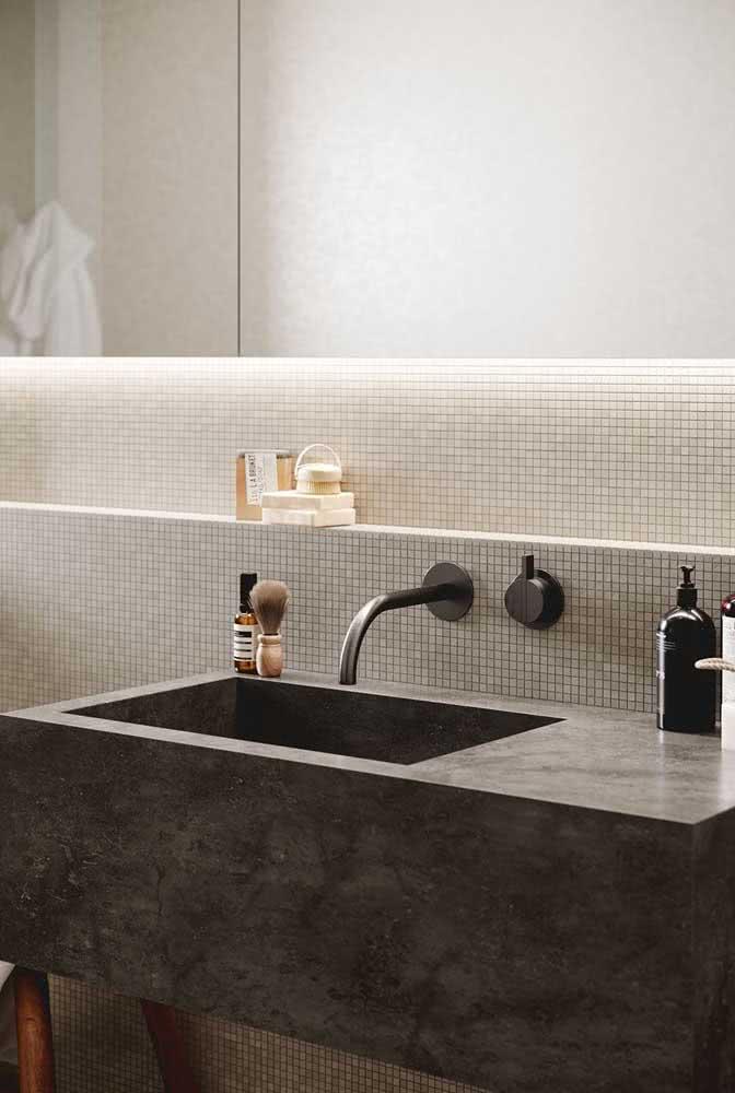 Bancada de porcelanato para o banheiro com pia esculpida no próprio material. O efeito de cimento queimado é o grande destaque do projeto