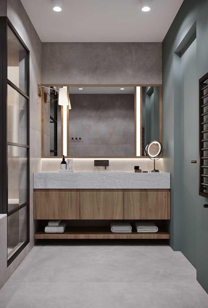 Bancada de porcelanato para o banheiro moderno. O gabinete de madeira deixa o projeto ainda mais completo e funcional