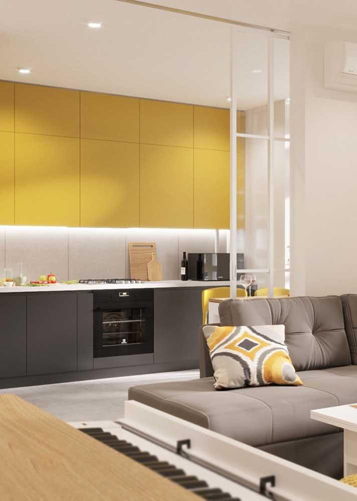 Cozinha amarela, branca e cinza integrada harmoniosamente com a sala de estar
