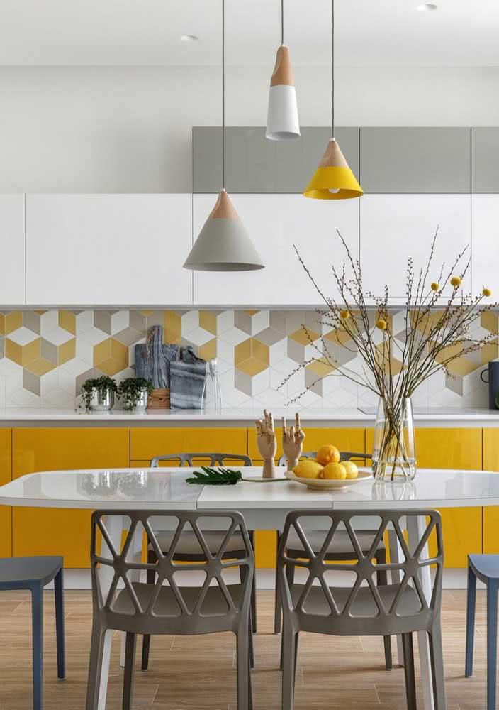 Cozinha amarela com toques de cor no revestimento, no armário e nas luminárias