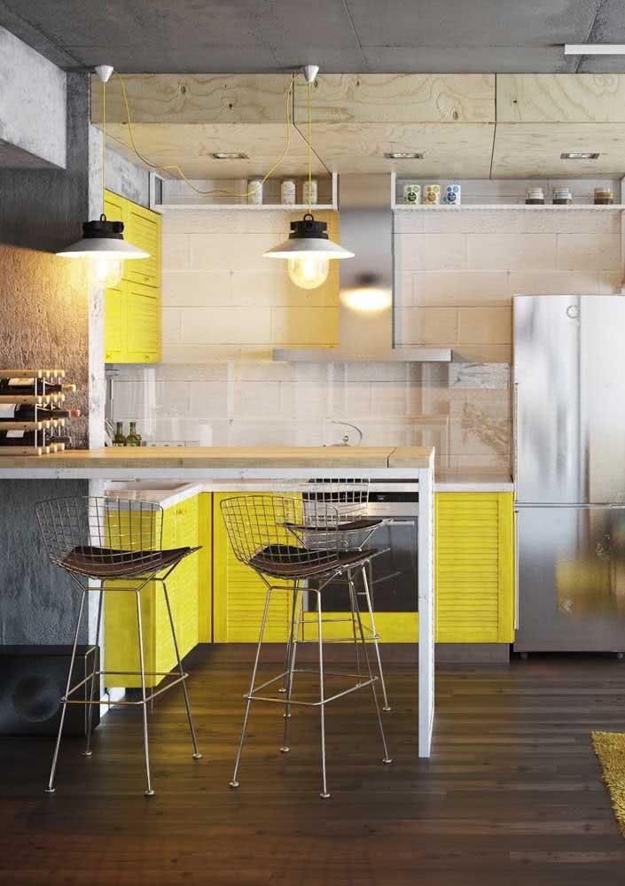 Moderna, essa cozinha amarela mescla madeira de pinus com concreto aparente