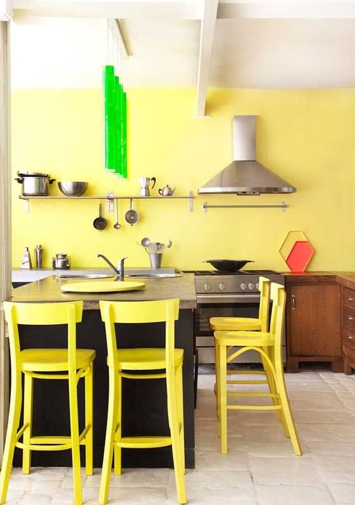 Amarelo claro na parede da cozinha combinando com as cadeiras