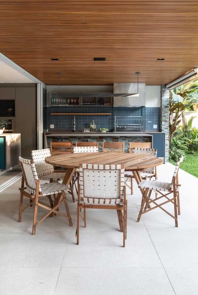 Área gourmet pequena integrada com o quintal gramado. Destaque para o contraste entre o piso claro e o forro de madeira