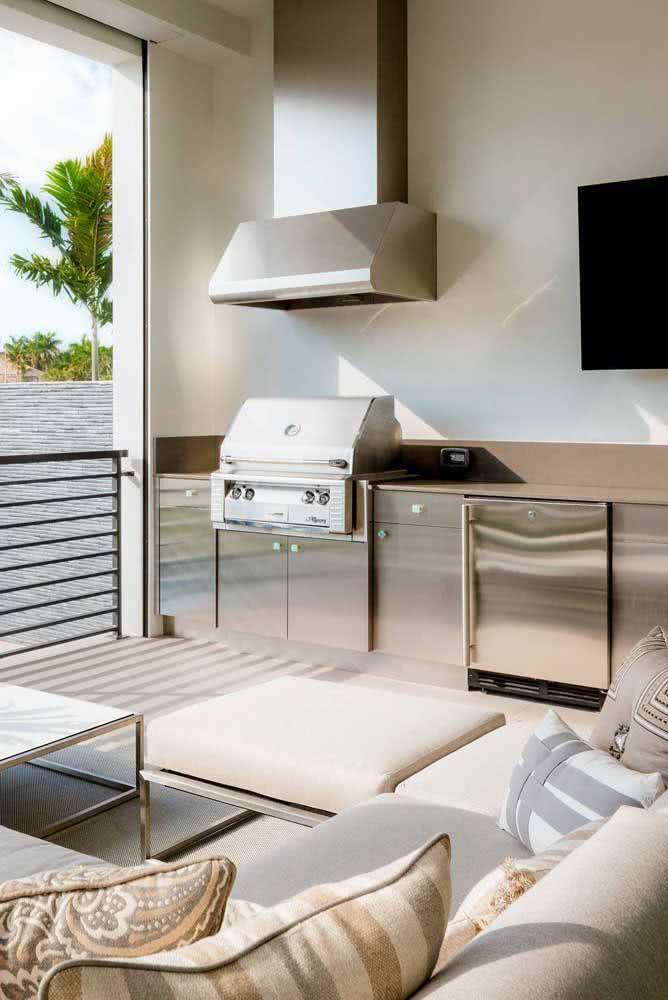Área gourmet pequena equipada com móveis de inox e churrasqueira elétrica