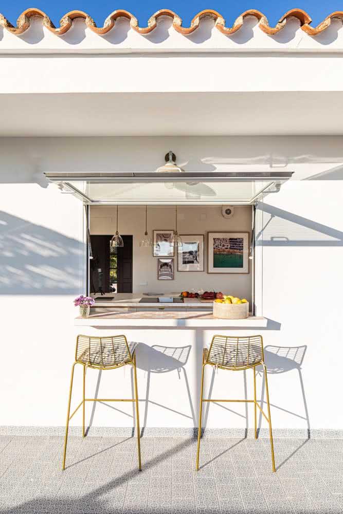 Um balcão para integrar a cozinha com a área gourmet pequena externa