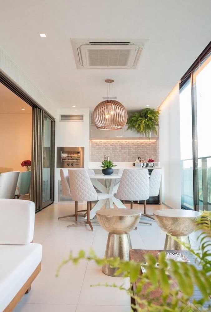 Área gourmet pequena e clean com móveis e revestimentos de cores claras e uma iluminação sob medida