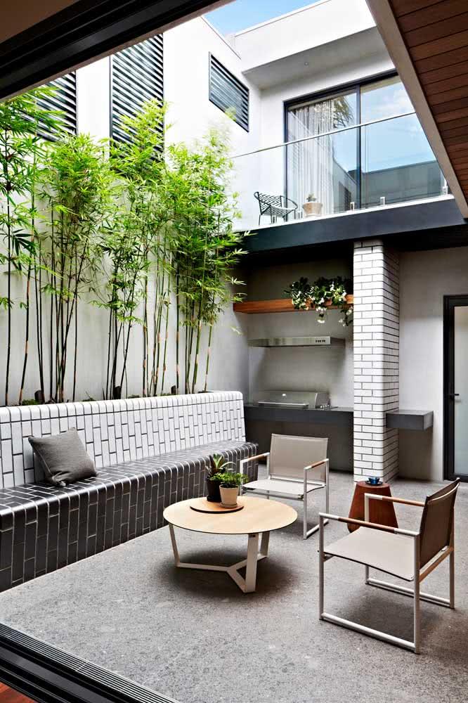 O banco de alvenaria garante o conforto da área externa, faça chuva ou faça sol