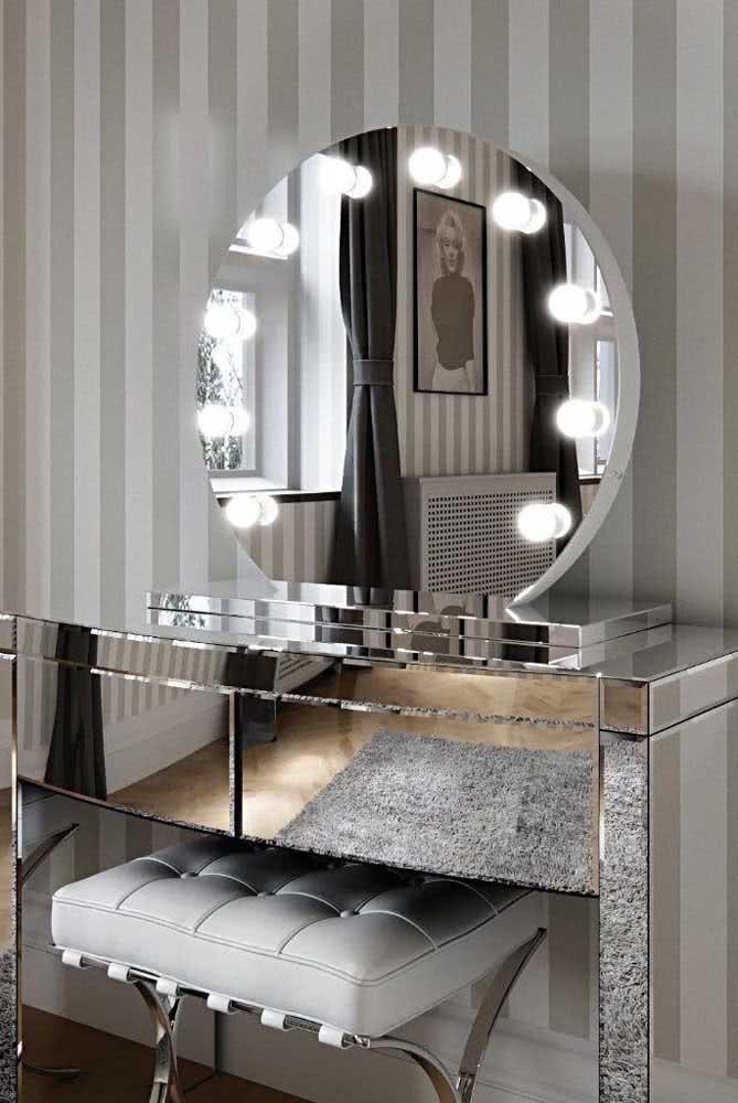 Um luxo esse espelho camarim redondo com lâmpadas acopladas junto da penteadeira espelhada
