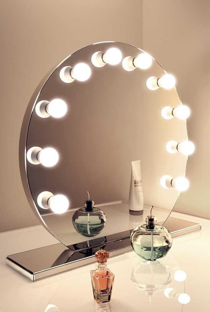 Aqui, a base metálica serve como apoio para o espelho camarim redondo e pequeno