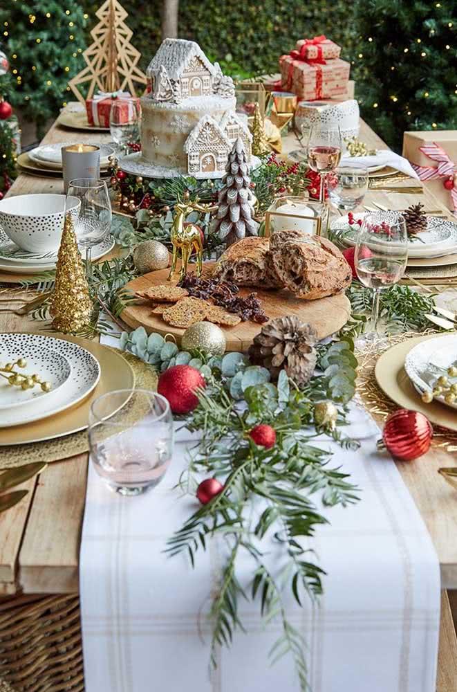 Mesa posta decorada com festão de natal, frutas e outros enfeites