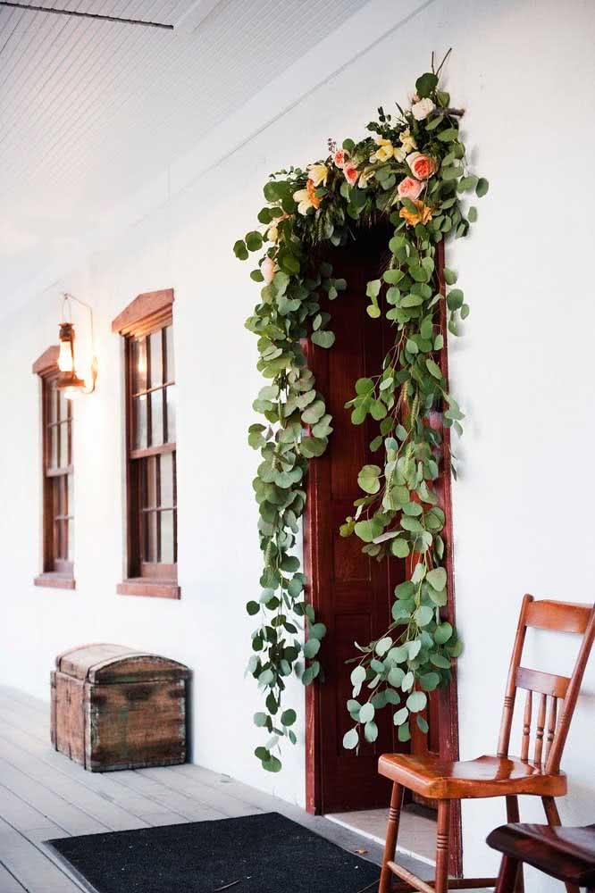 Porta de entrada decorada com festão de folhas naturais