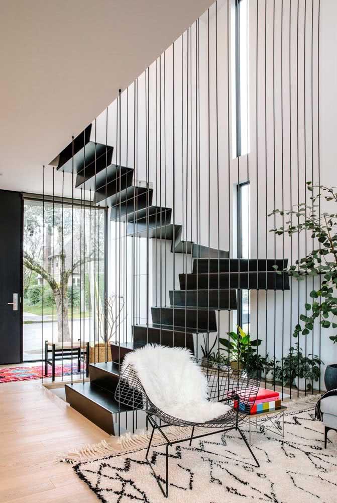 Aqui, a cadeira Bertoia preta parece conversar diretamente com o estilo do guarda corpo da escada