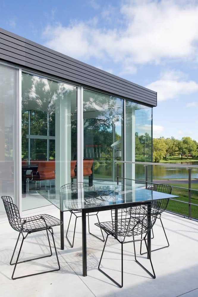 Cadeira Bertoia preta na área externa da casa. O material usado na fabricação permite que a peça seja usada tranquilamente em ambientes externos
