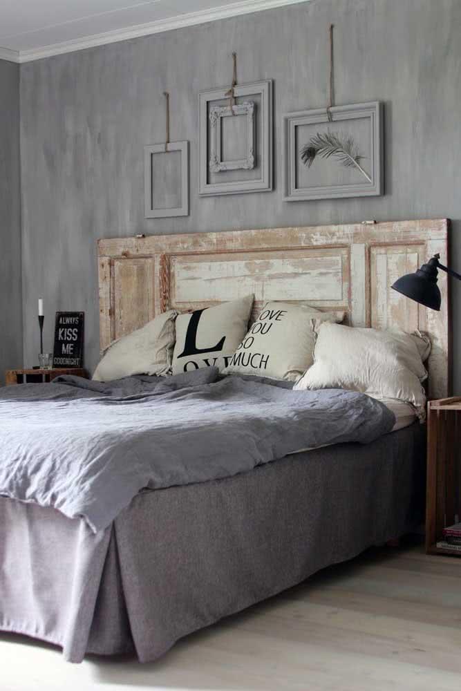 Quarto rústico de casal moderno decorado em tons de cinza e uma cabeceira feita com porta de madeira