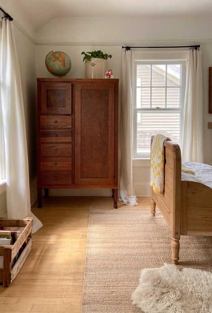 Móveis antigos de madeira são a cara de um quarto rústico