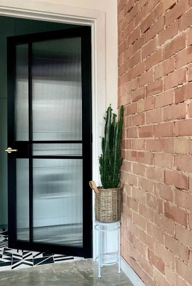 Porta de entrada com vidro canelado. A esquadria preta garante um toque moderno à peça