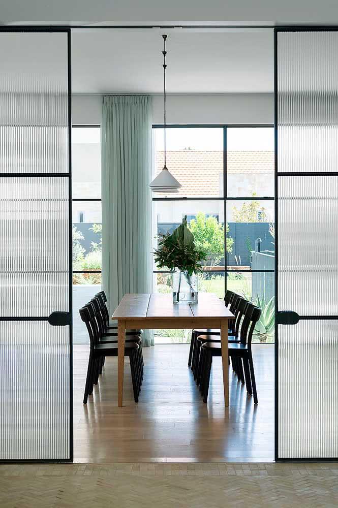 Porta de correr com vidro canelado dividindo a sala de jantar da sala de estar