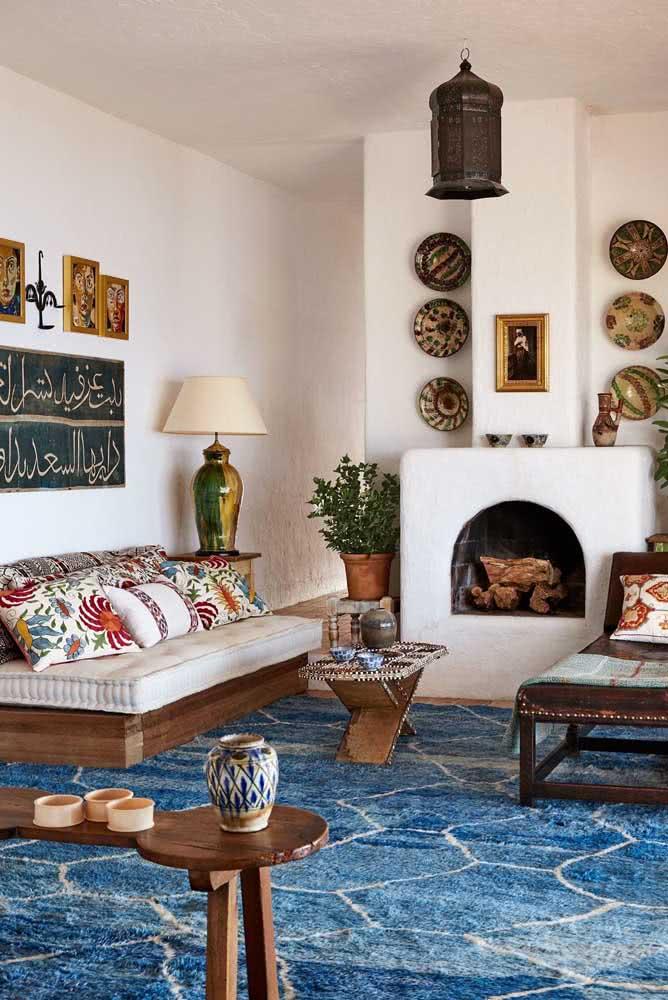 Ideia de decoração árabe para sala de estar. Aqui se destacam as luminárias, o tapete e a escrita árabe na parede