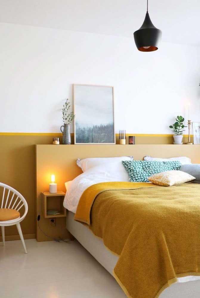 Quarto acolhedor e minimalista. Aqui, a roupa de cama mostarda e a pintura na parede quebram a neutralidade do branco