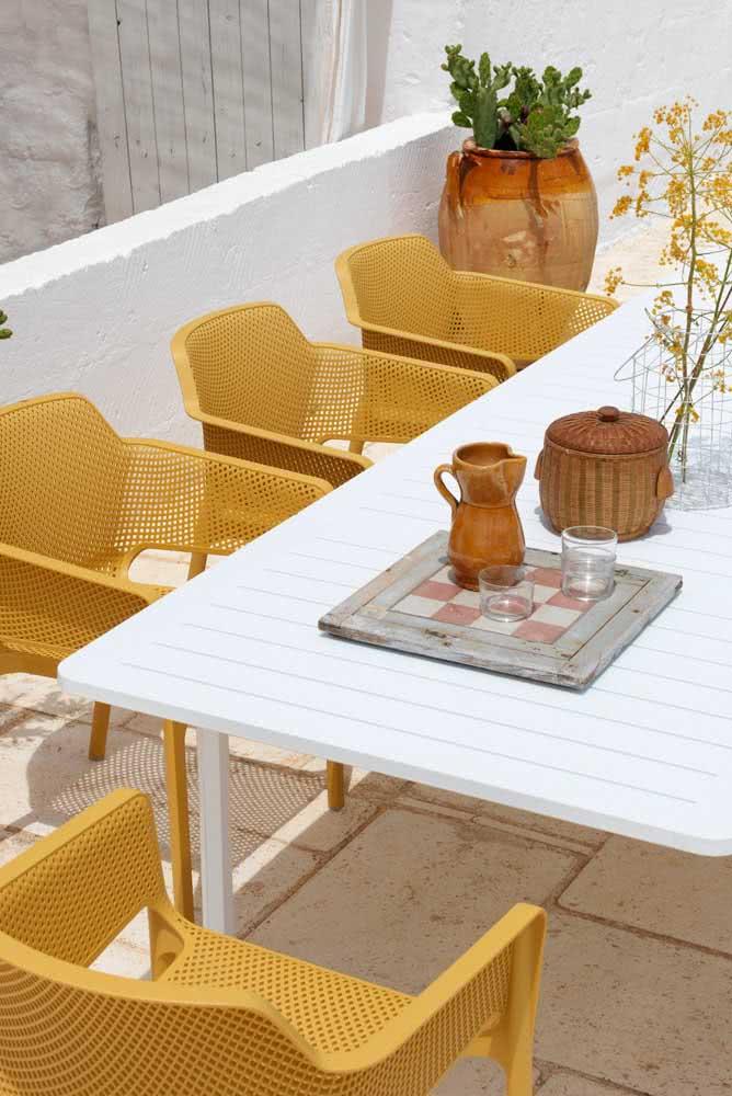 Cadeiras mostarda na área externa para realçar o calor e a luz do sol