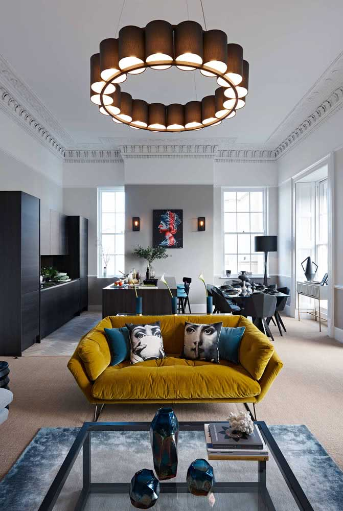 Uma sala de tons neutros com um sofá mostarda capaz de acabar com a monotonia