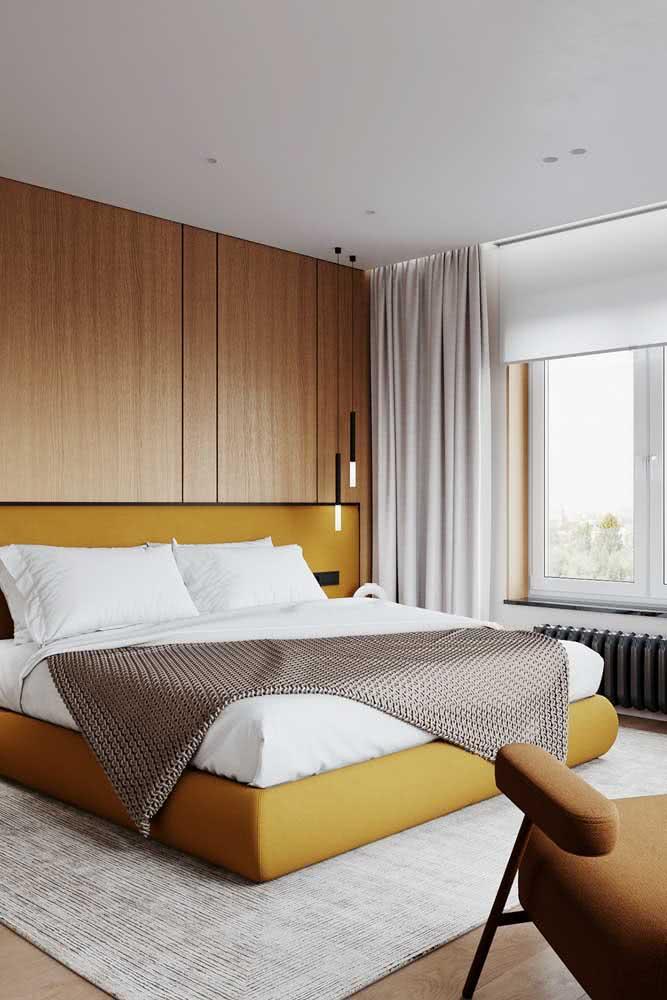 Cama mostarda realçada pelo painel de madeira. Um quarto moderno e aconchegante ao mesmo tempo