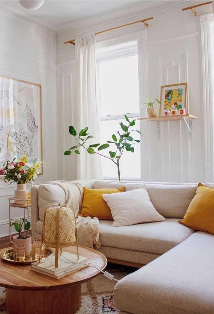 Nessa sala boho e rústica, a cor mostarda aparece nos detalhes, como a capa das almofadas e o quadro na parede