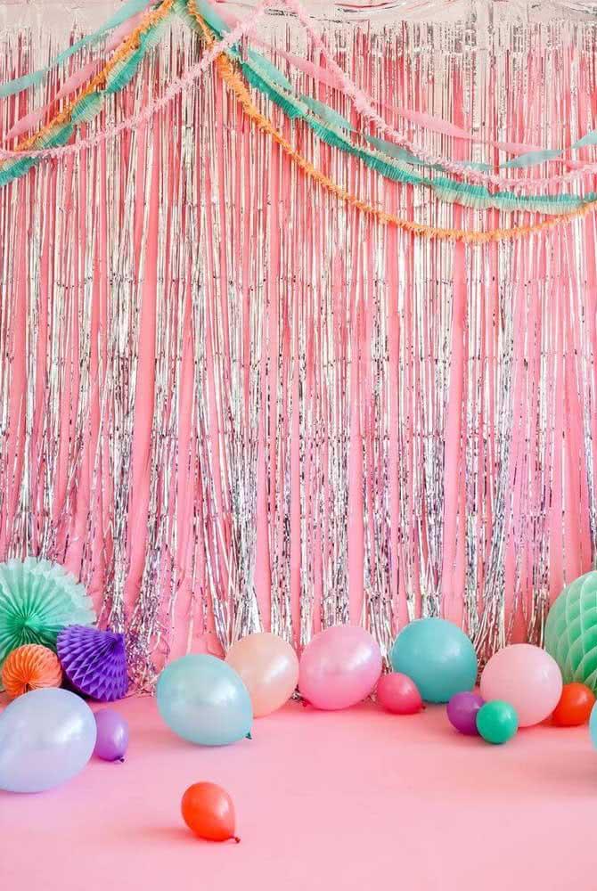 Vitrine de carnaval simples decorada com fitas prateadas sobre o fundo rosa. Os balões finalizam a proposta