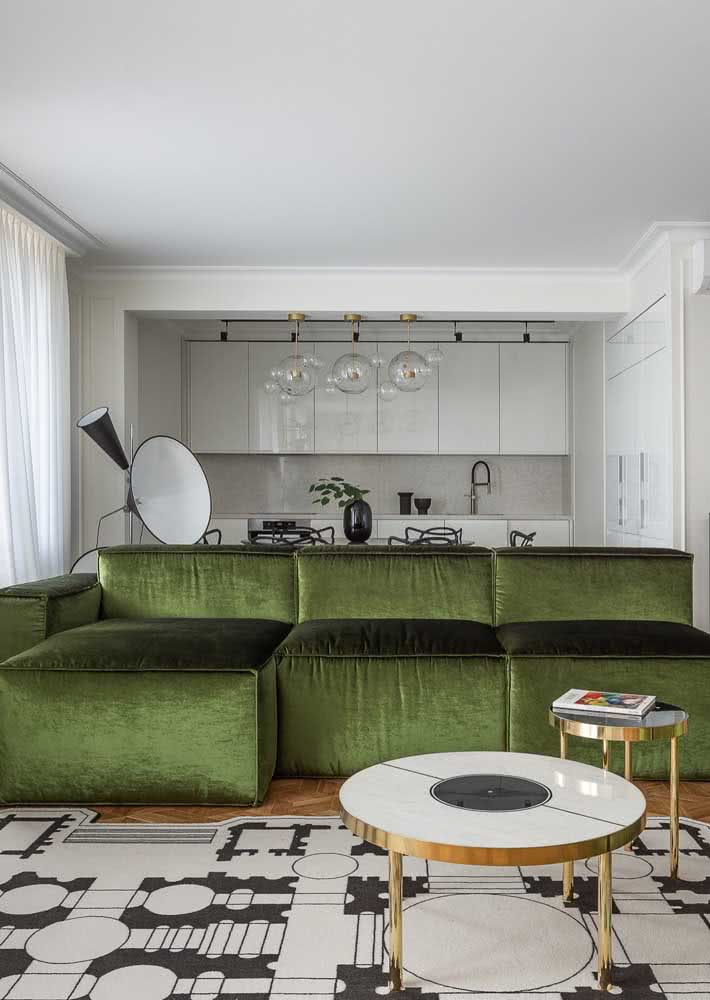 Para o ambiente integrado e decorado em tons neutros, o sofá verde se tornou o ponto focal