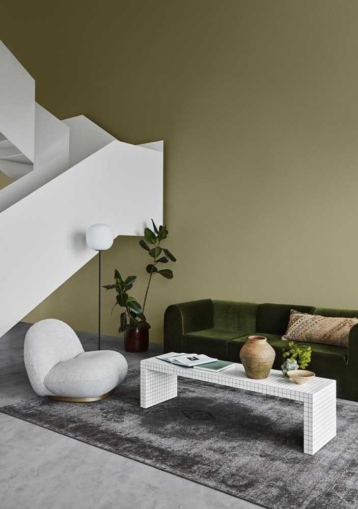 Decoração de sala com sofá verde e parede em tom terroso
