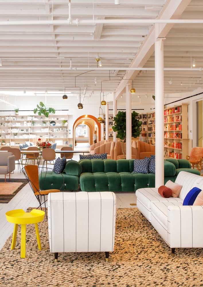 Uma casa moderna, integrada e com um sofá verde de veludo que é impossível não olhar